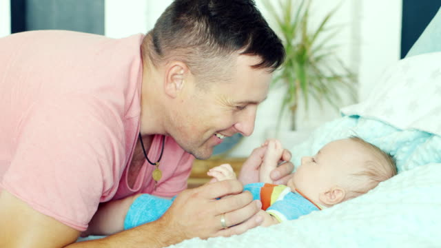 Young father playing with his son two months. he smiles video