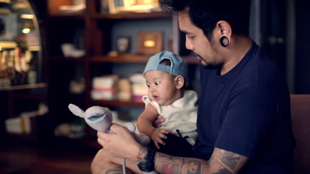 Young father playing with son holding doll on sofa video
