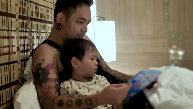 junger vater liest gutenachtgeschichten an seinen sohn im bett zu hause. - storytelling videos stock-videos und b-roll-filmmaterial