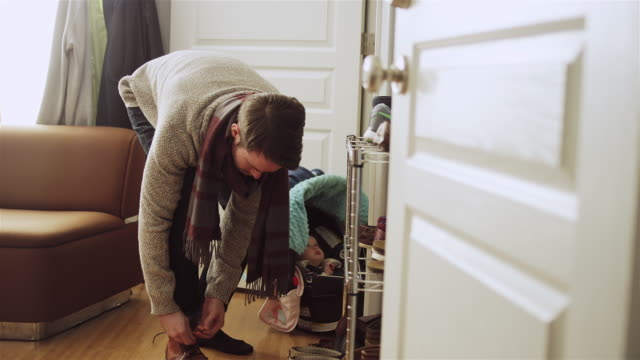 A young father ties his shoes while his daughter waits in her carseat video