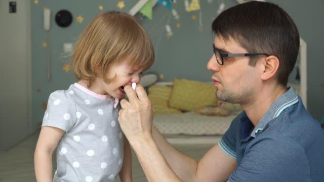 vídeos y material grabado en eventos de stock de joven padre con gafas gotea gotas de aerosol de la pequeña hija llorando lindo. - alergias alimentarias