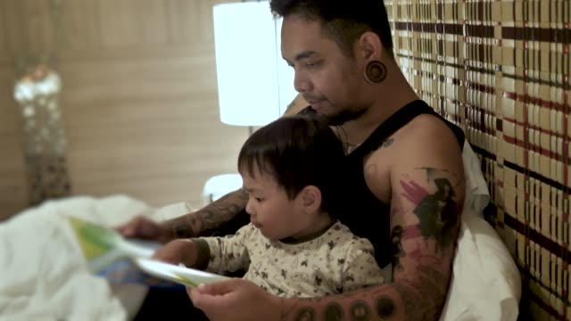 Young father with little son lying on bed at home and reading fairytale book before sleeping in video