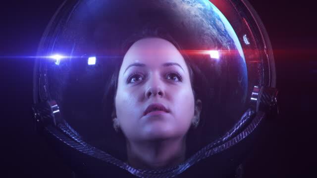 junge furchtlose schöne astronautin, die den unendlichen raum erkundet - raumanzug stock-videos und b-roll-filmmaterial