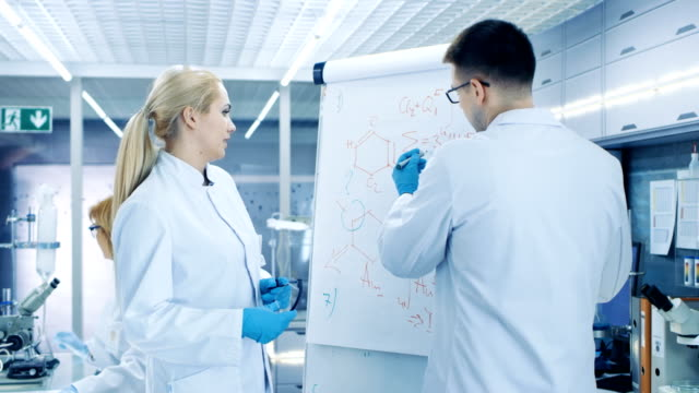 Young Female and Male Scientists Write Formulas on a Whiteboard. They're Solving Scientific Problems in Bright Modern High Tech Laboratory. video