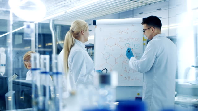 Young Female and Male Scientists Write Formulas on a Whiteboard. They're Solving Scientific Problems in Bright Modern High Tech Laboratory. Young Female and Male Scientists Write Formulas on a Whiteboard. They're Solving Scientific Problems in Bright Modern High Tech Laboratory. Shot on RED EPIC-W 8K Helium Cinema Camera. chemical formula stock videos & royalty-free footage