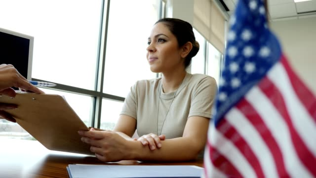 Young female army soldier applies for loan from bank Unrecognizable loan officer explains loan application to female army soldier. The soldier nods her head in understanding while listening to the loan officer. military lifestyle stock videos & royalty-free footage
