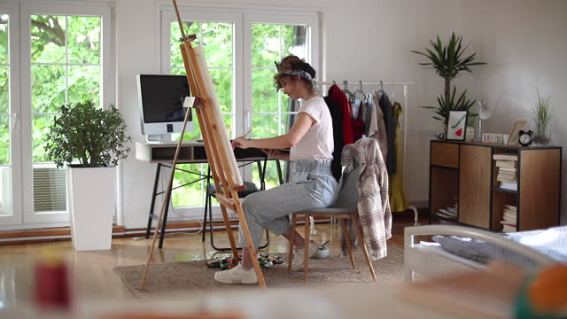 Young female artist painting video
