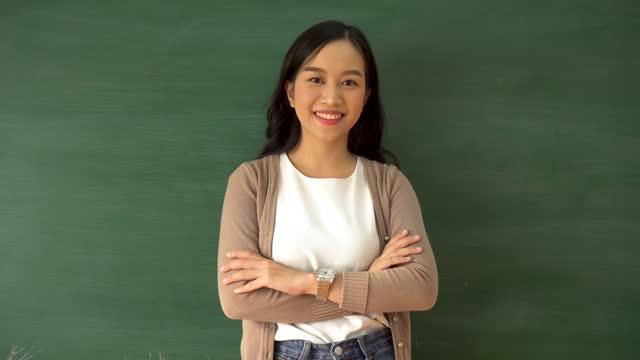 stockvideo's en b-roll-footage met jonge vrouwelijke aziatische leraar die door schoolbord in schoolklaslokaal glimlacht - aziatische etniciteit