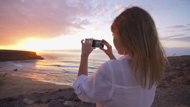 Young female at beach taking pictures of sunset with phone video