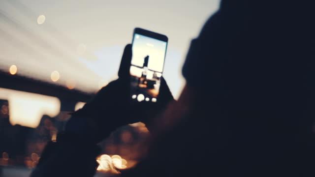 스마트폰으로 다리의 사진을 찍고 강에 젊은 여성 - 영화 촬영 스톡 비디오 및 b-롤 화면