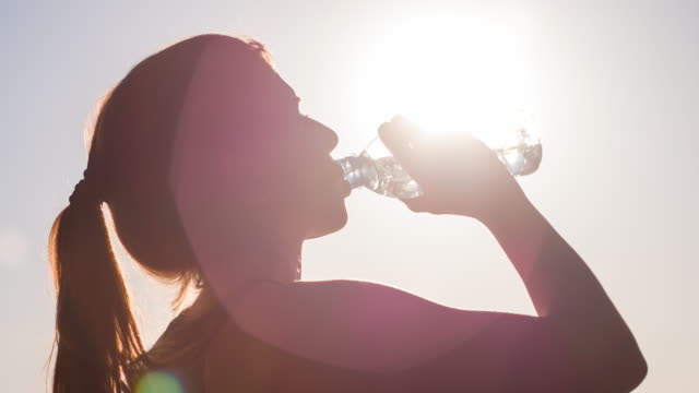 Young female athlete drinking isotonic drink after high intensity workout video