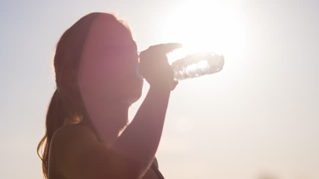 Young female athlete drinking water after working out video