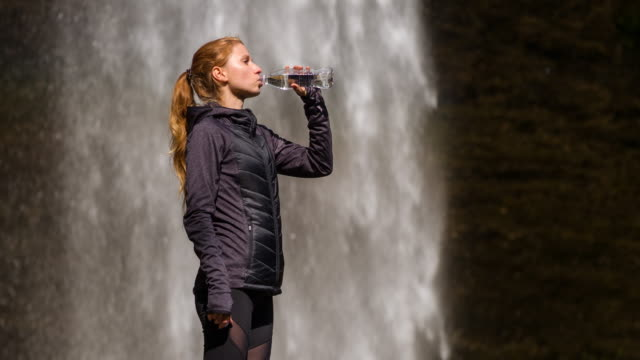 Young female athlete drinking water in front of a waterfall video