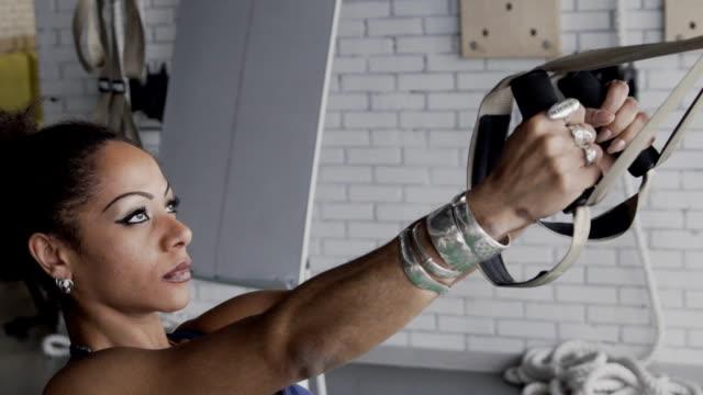 vídeos de stock, filmes e b-roll de jovem atleta feminina está dando certo com loops de trx no clube desportivo - fuso horário