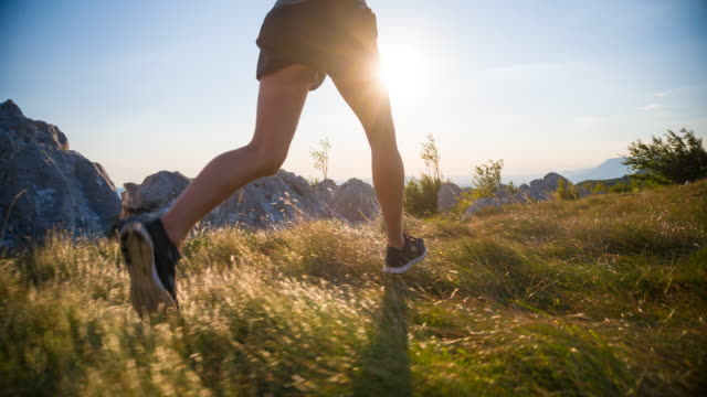 unga kvinnliga idrottare som kör i bergen vid solnedgången - jogging hill bildbanksvideor och videomaterial från bakom kulisserna