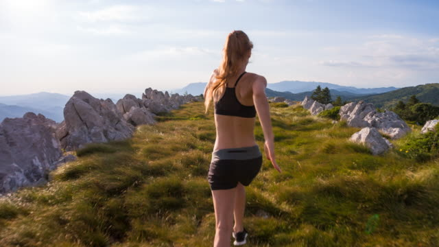 Young female athlete running on a meadow in the mountains video