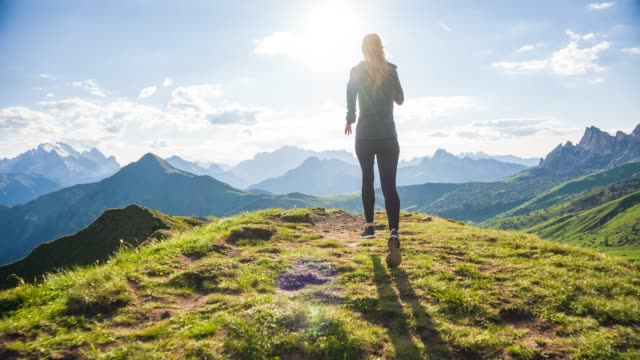 Young female athlete running on grassy trails towards the sun in mountain terrain