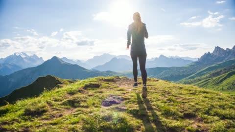 vidéos et rushes de jeune athlète femelle fonctionnant sur des sentiers herbeux vers le soleil dans le terrain de montagne - en haut