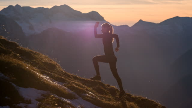 Young female athlete running up the mountain at sunset video