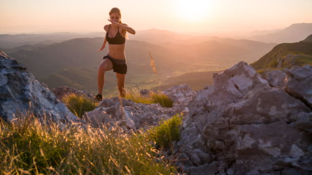 Young female athlete running up the mountain at sunset Young female runner training in the mountains at sunset, running towards the camera. conquering adversity stock videos & royalty-free footage