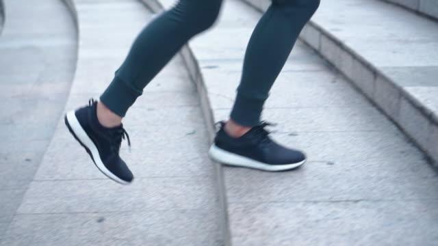 young female athlete running up the stairs,slow motion - biegać filmów i materiałów b-roll