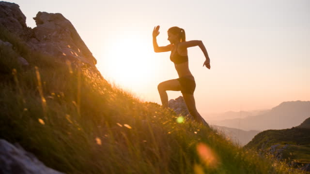 Young female athlete running uphill at sunset Young female runner training in the mountains at sunset. conquering adversity stock videos & royalty-free footage