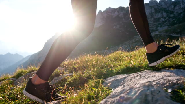 Young female athlete walking up a mountain Young woman walking uphill. human foot stock videos & royalty-free footage