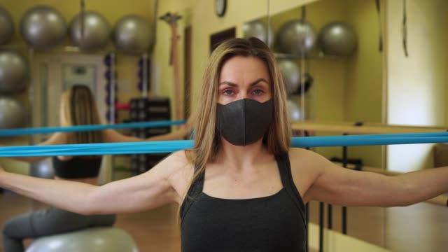 stockvideo's en b-roll-footage met jonge vrouwelijke atleetvrouw die zwart beschermend masker rekt blauwe rubberweerstandsbandoefeningen in lege gymnastiek op quarantaine. atleten zijn sterk om covid-19 te stoppen - mirror mask