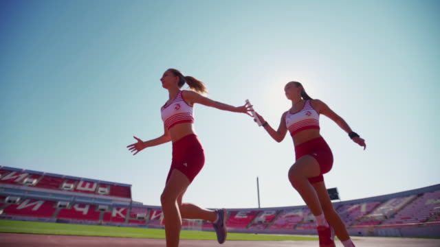young female athletics exchanging relay baton - атлет стоковые видео и кадры b-roll