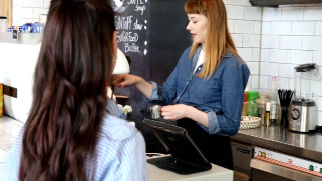 カフェでお客様と話している若い女性バリスタ ビデオ