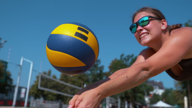 SLOW MOTION: Young female beach volleyball player receives and passes the ball. SLOW MOTION, CLOSE UP: Young female beach volleyball player receives and passes the ball during a competition. Cinematic shot of focused Caucasian woman in bikini playing volleyball in the summer heat volleyball sport stock videos & royalty-free footage