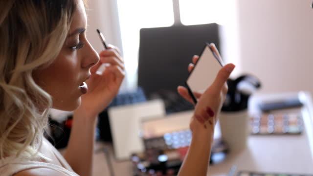 自宅で化粧化粧品と若い女性のブロガーの録音 vlog - アイシャドウ点の映像素材/bロール