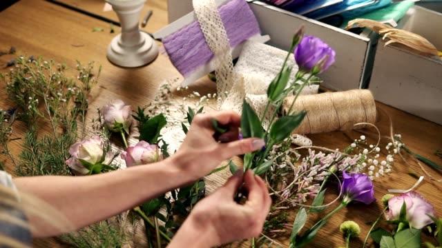 vidéos et rushes de jeune femme fleuriste blonde préparation pour le bouquet de fleurs. mains du propriétaire de magasin de fleurs à son magasin de fleurs en bouquet. fleur de coupe fleuriste découle au magasin de fleurs. slow motion shot - composition florale