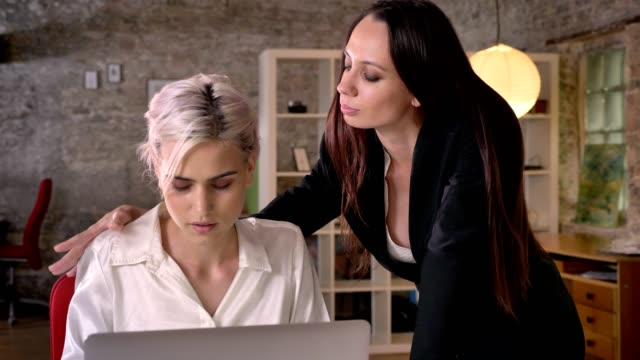 stockvideo's en b-roll-footage met jonge vrouwelijke baas flirten met haar vrouwelijke werknemer in moderne kantoor, geërgerd door intimidatie van lesbische vrouw - verleiding
