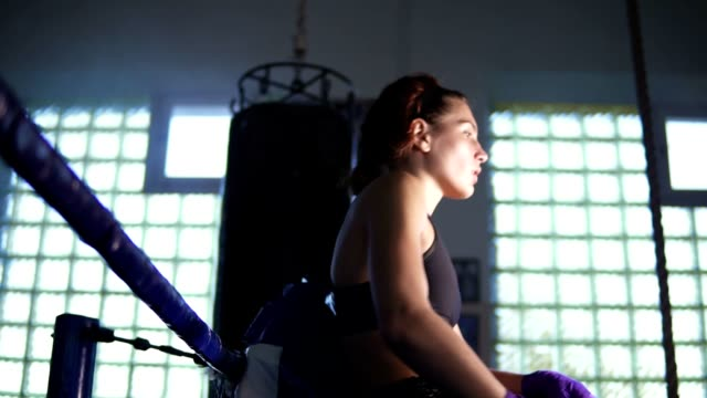 Young female boxer coming to the corner of the boxing ring and resting with her arms on the ring ropes in the dark gym. Slowmotion shot video