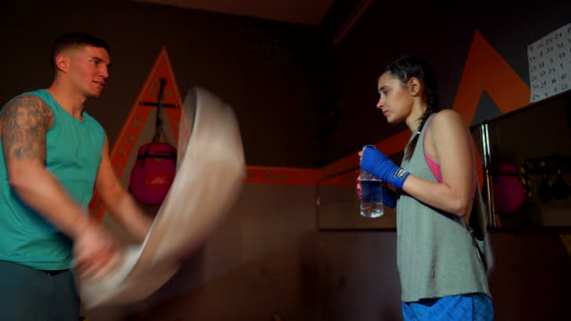 Young female boxer drinks water after an exhausting training and the coach cools her down with a towel
