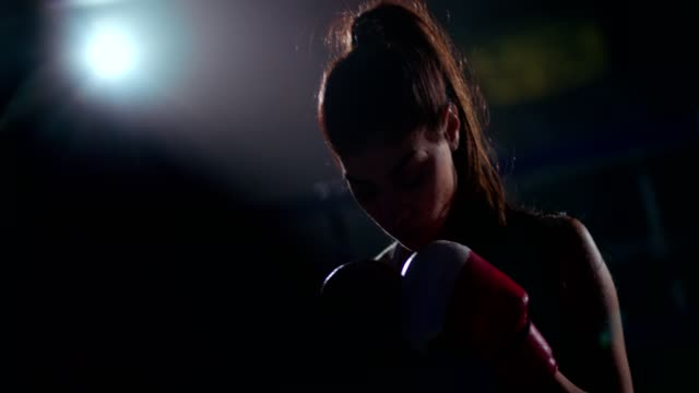 Young female boxer getting ready for a night fight video