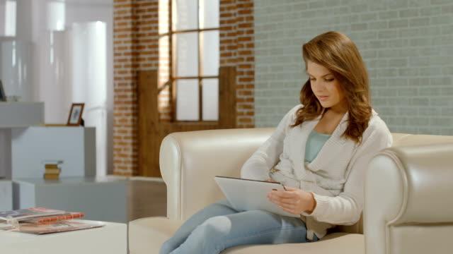 молодая женщина, просматривая интернет на планшете пк, улыбается в камеру - google стоковые видео и кадры b-roll