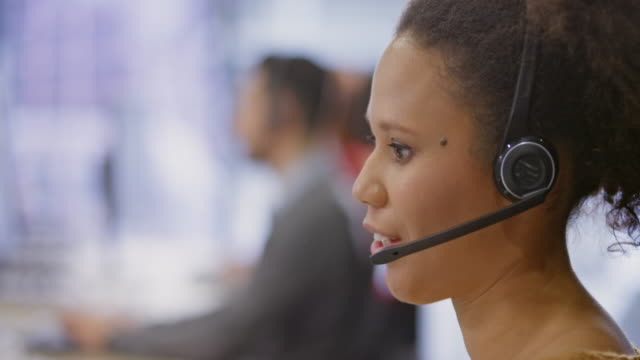 LD Young female call centre agent talking with headphones