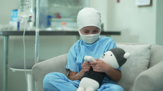 Young female cancer patient wearing headscarf and mask 9 year old cancer patient sitting in hospital with an IV while cuddling with her favorite stuffie for comfort. oncology stock videos & royalty-free footage
