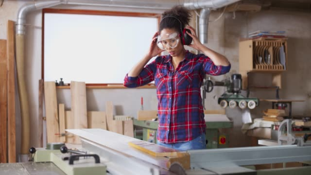 ds young female carpenter setting the table saw in the workshop - occhiali protettivi video stock e b–roll