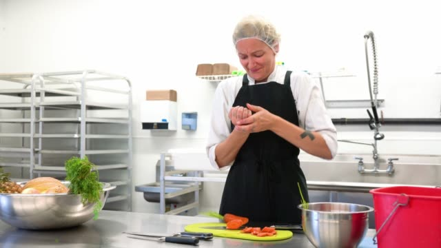 a young female chef in a hair net cuts herself while chopping vegetables. - rana filmów i materiałów b-roll