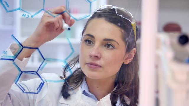 Young female chemist confidently draws formula on transparent board video
