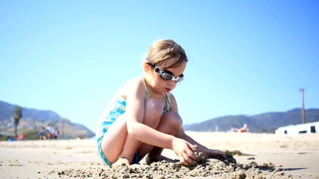 Young female child playing with sand on beach video