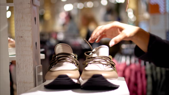 a young female chooses new sneakers in the store - shoes fashion stock videos and b-roll footage