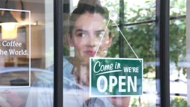 young female coffee shop owner opening the shop - open sign stock videos & royalty-free footage