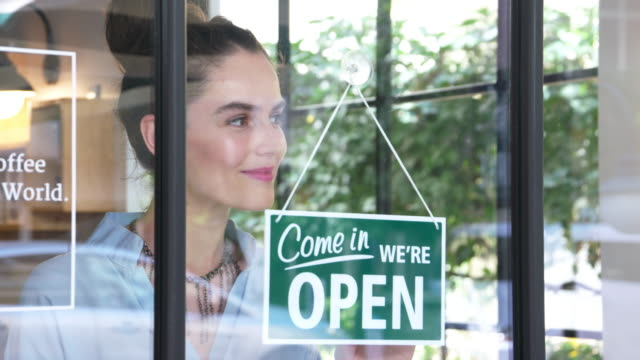 Young female coffee shop owner opening the shop