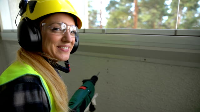 Young Female construction worker drilling concrete wall with a drill and smiling at the camera. Slow motion video