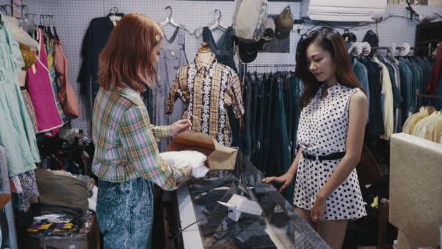 リサイクルショップでヴィンテージ衣料品を支払う若い女性顧客 - オペレーター 日本人点の映像素材/bロール