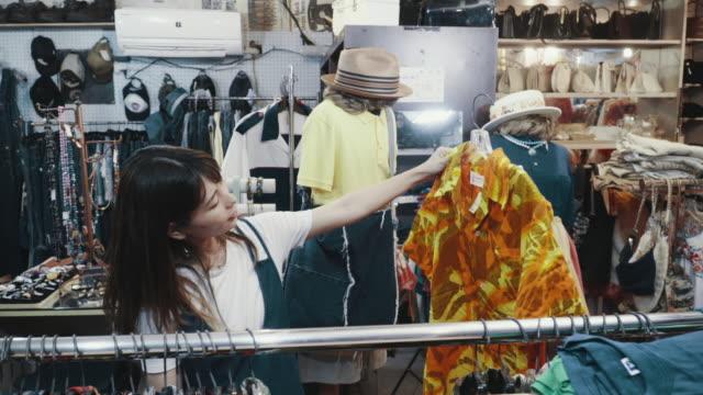 リサイクルショップでヴィンテージ衣料品を買う若い女性客 - オペレーター 日本人点の映像素材/bロール